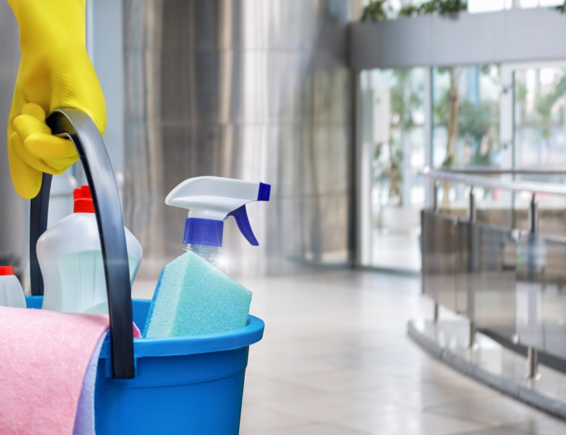 Cleaning lady with a bucket and cleaning products before washing the floor.